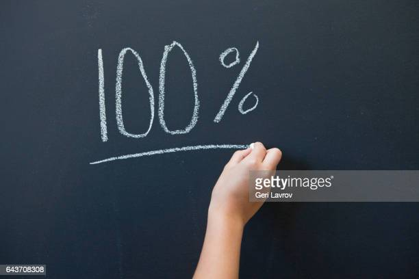 A child writing the word 100% on a blackboard