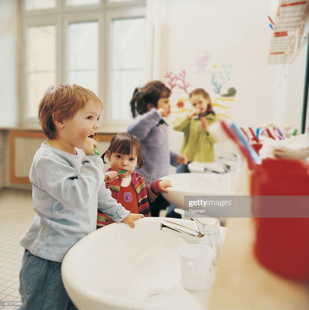 Childern in a Nursery Bathroom Brushing their Teeth : Stock Photo