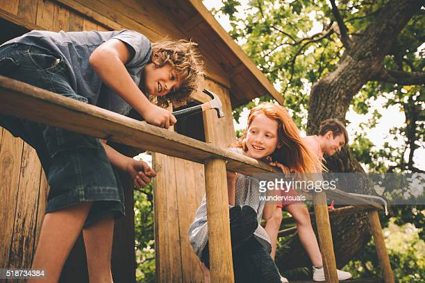 Childhood friends hammering and working to build their treehouse