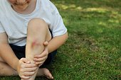 Young boy holds a sore leg that received a injury while playing outdoors.