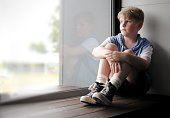 Young boy sits looking out a window.