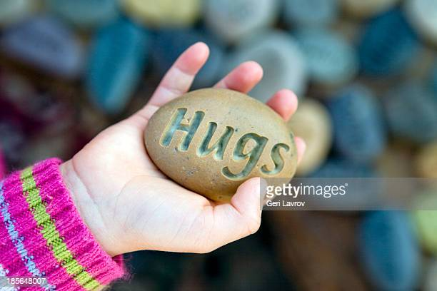 Childing holding a stone with 'hugs' engraved