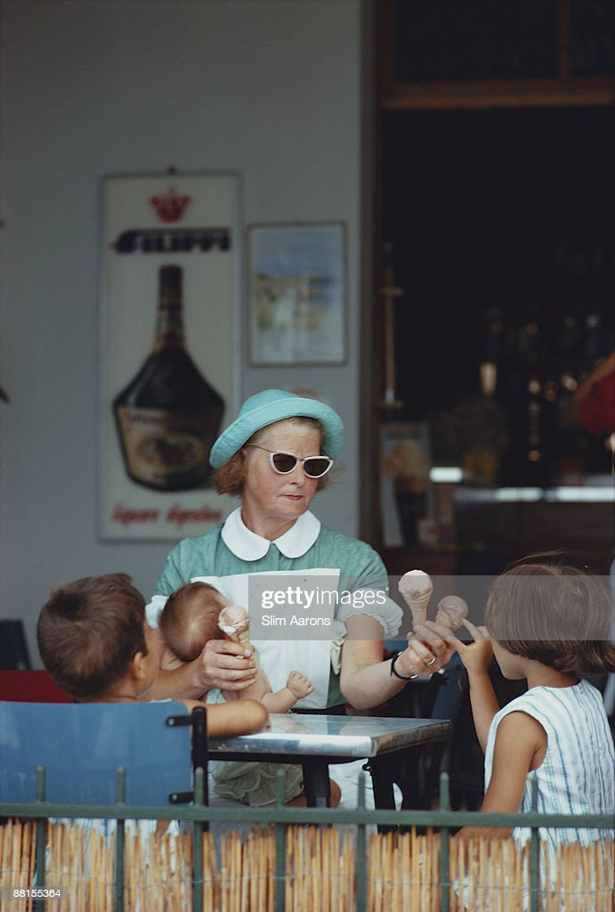 A childminder hands out ice creams to her charges at a cafe, Italy, August 1967.