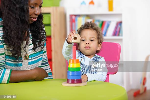 Childminder Supervising Toddler Playing With Developmental Wooden Toy.