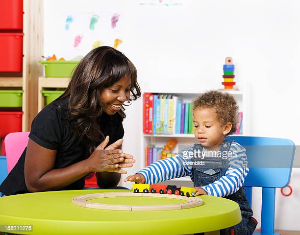 Childminder/Carer Encouraging Toddler During Playtime