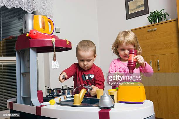 Children, 2 and 3 years, playing with toy kitchen