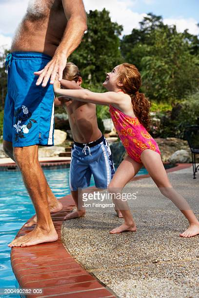 Children 5-8) pushing grandfather into pool, side view