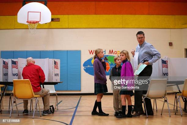Children accompany their father as he votes at the polling place in the gymnasium at Washington Mill Elementary School November 7 2017 in Alexandria...