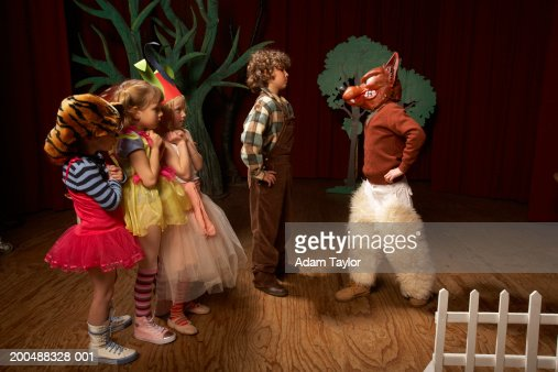 Children 5-12 acting on stage one boy confronting bad wolf  Stock Photo