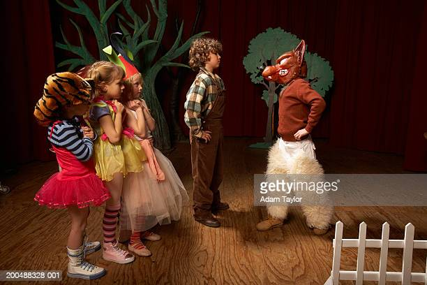 Children (5-12) acting on stage, one boy confronting bad wolf