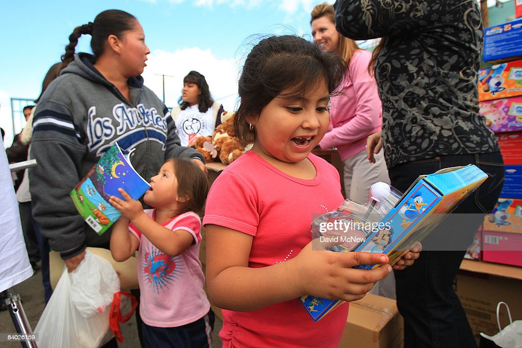 Children admire their toys as people receive gifts of food, personal care and household items and toys at the Miracle in South Central event, part of the nationwide Miracle on Main Street, USA program to help working poor and disadvantaged families on December 13, 2008 in the South Central neighborhoods of Los Angeles, California. About 5,000 families are expected to receive enough food at the event to supplement meals for a family of four for a week. Miracle on Main Street, USA is sponsored by The National Basketball Players Association (NBPA) along with Feed The Children, Feed 333, Humanity Unites Brilliance (HUB) and hosted by the Salvation Army.