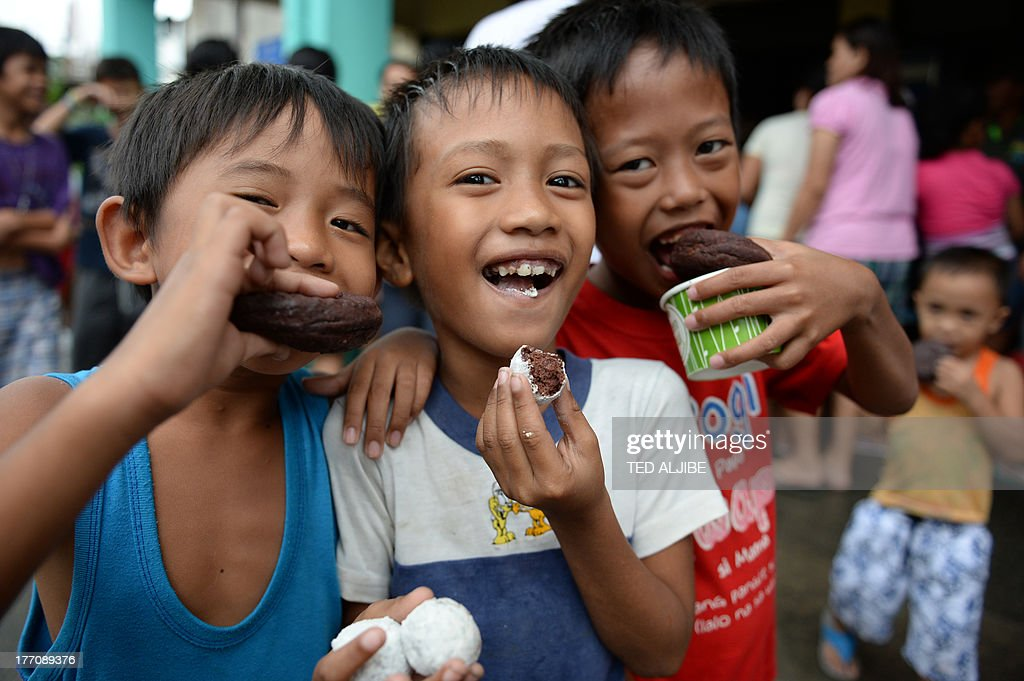 Children affected by flooding due to heavy rains exacerbated by Tropical Storm Trami smile after receiving free donuts inside a school building serving as an evacuation center in Marikina, east of Manila on August 21, 2013, as rains pounded the capital city for the third day. Heavy rain pounded the Philippine capital and surrounding areas for a third day August 21, adding to the misery of nearly 300,0000 exhausted people displaced from their flooded homes.