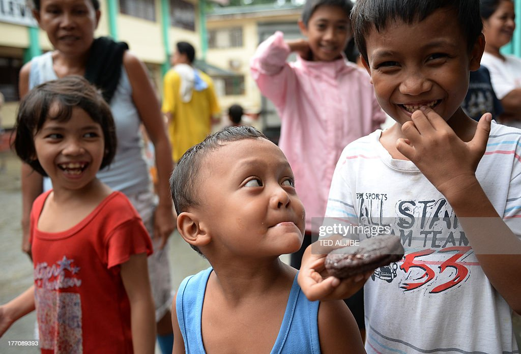 Children affected by flooding due to heavy rains exacerbated by Tropical Storm Trami smile after receiving free donuts inside a school building serving as an evacuation center in Marikina, east of Manila on August 21, 2013, as rains pounded the capital city for the third day. Heavy rain pounded the Philippine capital and surrounding areas for a third day August 21, adding to the misery of nearly 300,0000 exhausted people displaced from their flooded homes. AFP PHOTO / TED ALJIBE