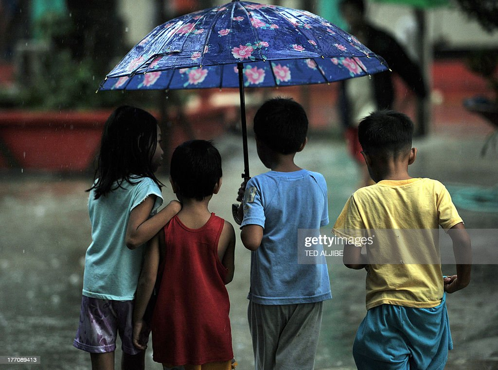 Children affected by flooding due to heavy rains exacerbated by Tropical Storm Trami share an umbrella after receiving free donuts at a school building serving as an evacuation center in Marikina, east of Manila on August 21, 2013, as rains pounded the capital city for the third day. Heavy rain pounded the Philippine capital and surrounding areas for a third day August 21, adding to the misery of nearly 300,0000 exhausted people displaced from their flooded homes.