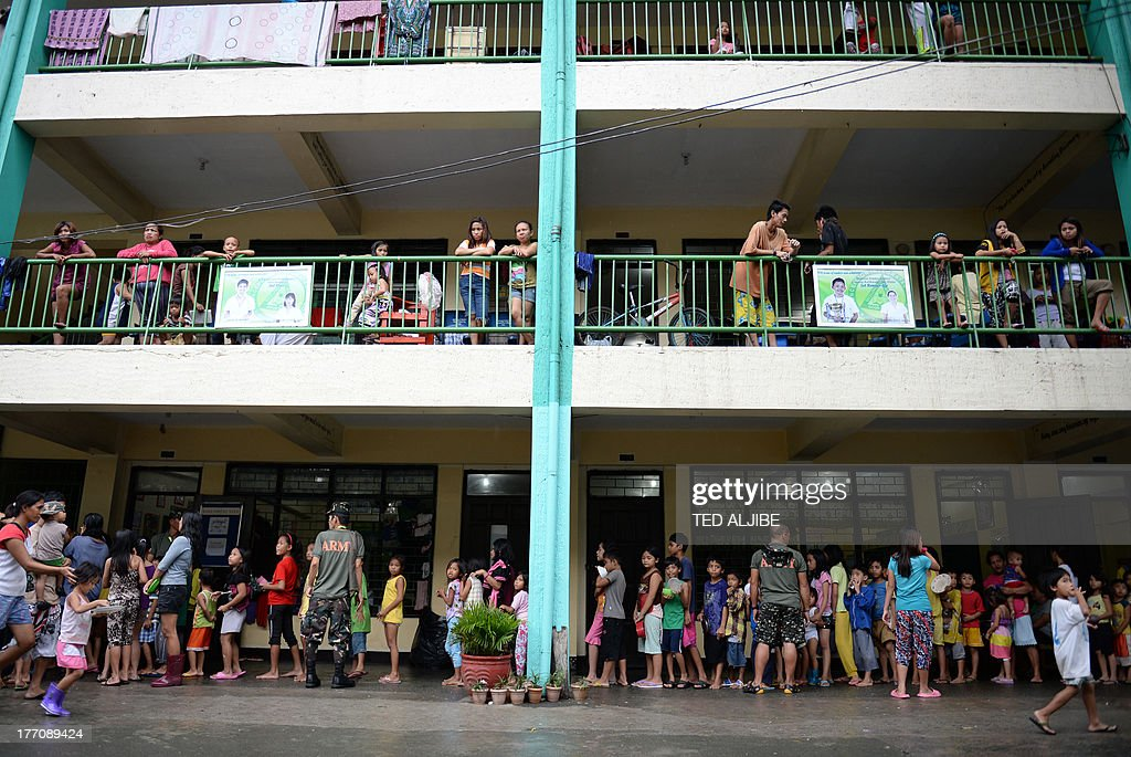 Children affected by flooding due to heavy rains exacerbated by Tropical Storm Trami queue up to receive free donuts inside a school building serving as an evacuation center in Marikina, east of Manila on August 21, 2013, as rains pounded the capital city for the third day. Heavy rain pounded the Philippine capital and surrounding areas for a third day August 21, adding to the misery of nearly 300,0000 exhausted people displaced from their flooded homes.