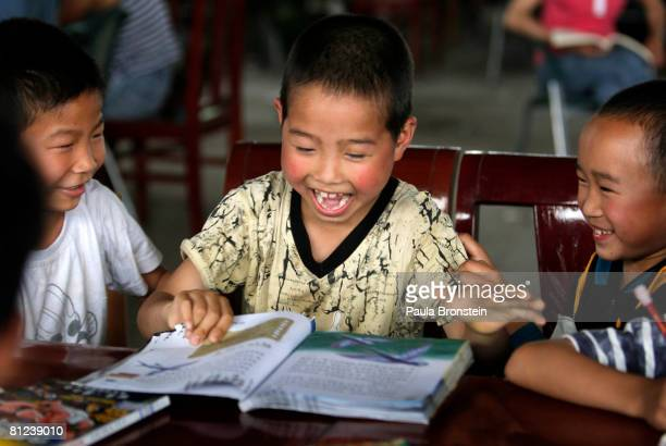 Children affected by the earthquake read donated books given to a refugee housing camp May 26 2008 in Dujiangyan Sichuan province China Caring for...