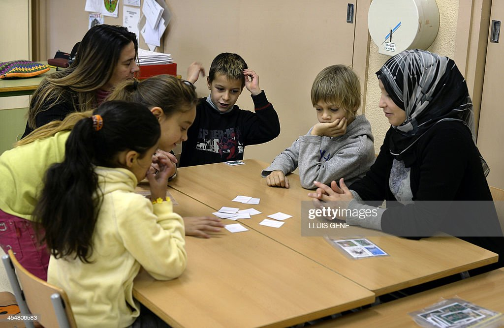 Children and adults attend a class at the Mediterrani language school in Tarragona on December 5 2013 Sitting behind small green desks several...