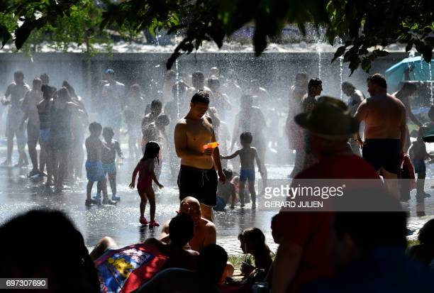 Children and adults cool off in fountains on the banks of the river Manzanares in Madrid on June 18 as temperatures rose high across Spain Spain goes...