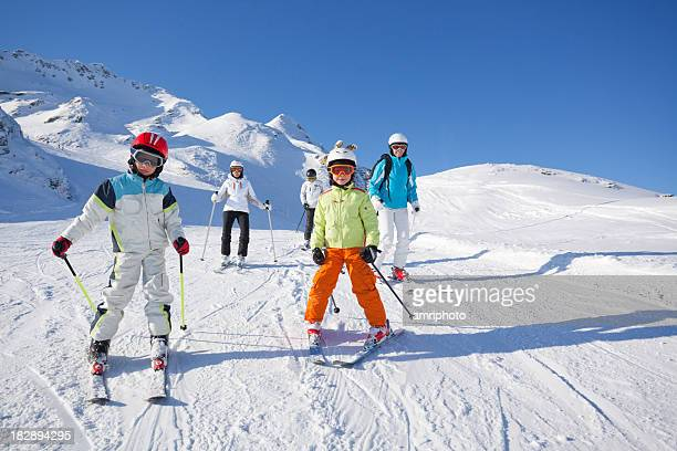 children and adults skiing on piste