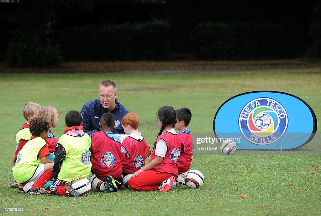 Children and an FA coach participate in a training session at St Marys Recreation Ground on July 31, 2013 in Harrow, England.