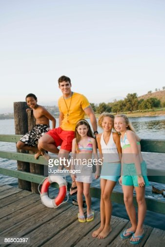 Children and camp counselor by lake : Stock Photo