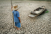 Children standing near the wooden boat on cracked earth. Metaphor for Global warming and Climate change.