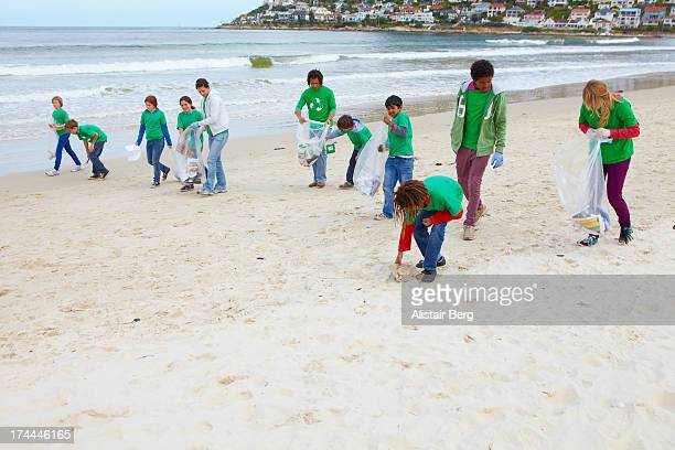 Children and community leaders cleaning beach