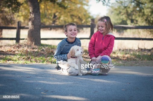 Children and Dog Sitting Together Outdoors : Stock Photo