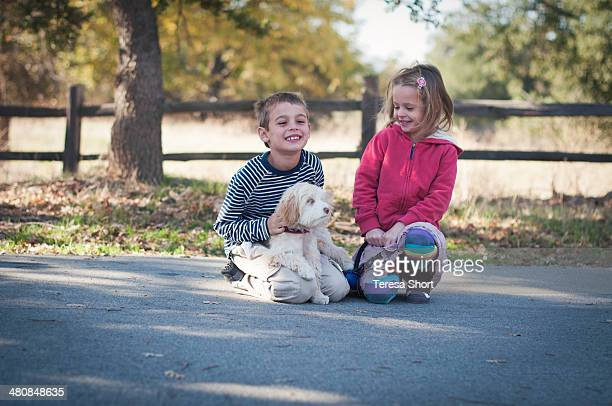 Children and Dog Sitting Together Outdoors