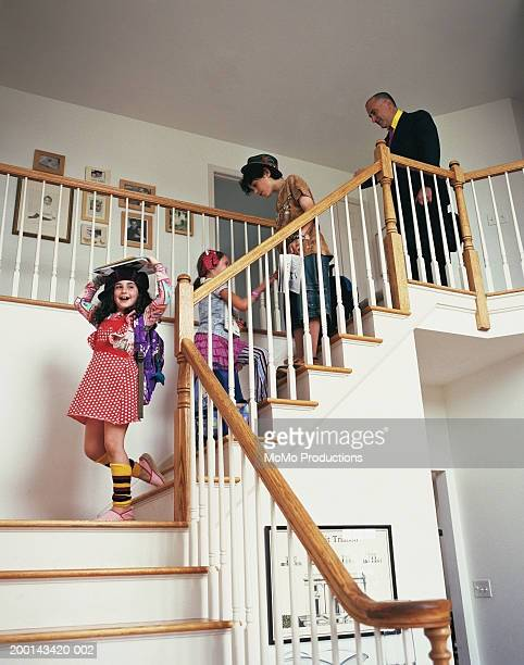 Children (5-12) and father walking down staircase with books