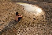 Child sit on the cracked earth and looking to the last pond on the lake. Metaphor for Global warming and Climage change.