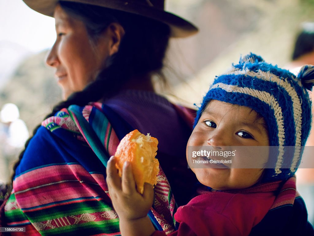 A children and her mother, wearing typical Andean wool dresses and hats, nearby the ruins of Písac, Valle de los Incas, Peru