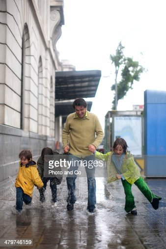 Children and men jumping and splashing in puddles