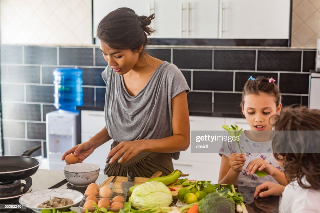 Children and Mother Cooking Healthy Food Together : Stockfoto