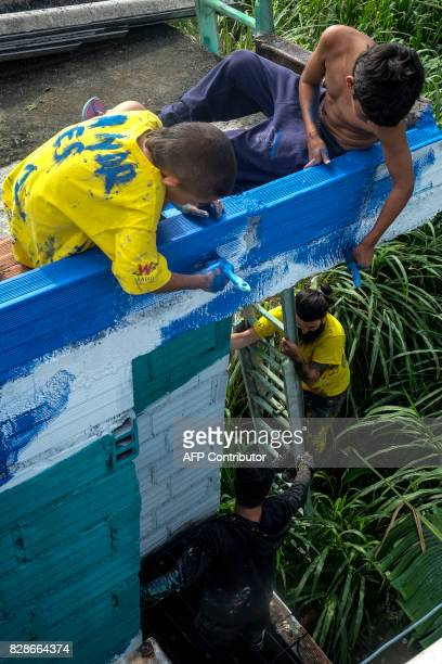Children and street artists paint the walls of El Pesebre shantytown in the outskirts of Medellin Colombia on June 30 2017 French artist Tarik...
