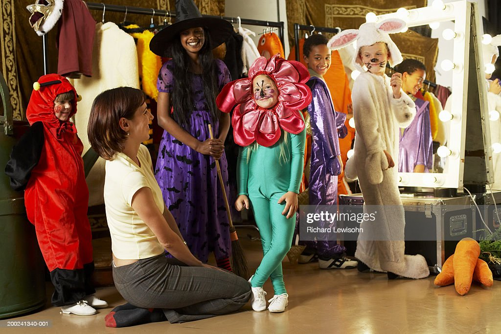 Children (5-9) and teacher backstage, portrait of girl in flower costume