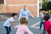 Happy multiethnic children having fun and playing ring around the rosie with teacher. School kids playing the game in summer camp. Pupils and cheerful woman holding hands all together and playing at s