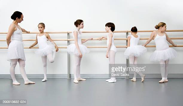 Children (9-13) and teacher resting at bar in ballet class