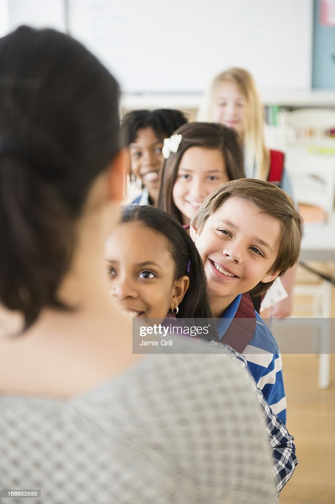 Children and teacher standing in row in classroom : Stock Photo