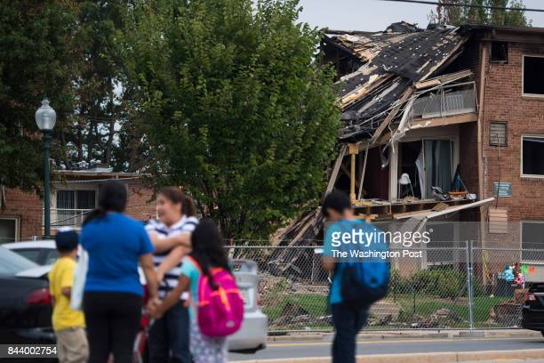 Children and their caretakers walk by the remains of the Flower Branch Apartments fire that killed 7 and left about 100 homeless last month as they...