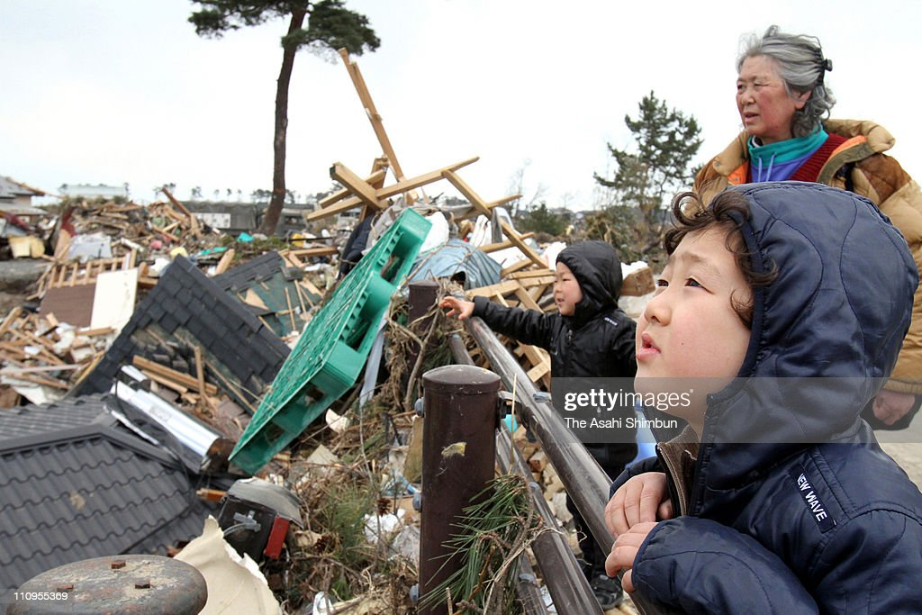 Children and their grandmother look the debris on March 28, 2011 in Higashimatsushima, Miyagi, Japan. The 9.0 magnitude strong earthquake struck offshore on March 11 at 2:46pm local time, triggering a tsunami wave of up to ten metres which engulfed large parts of north-eastern Japan, and also damaging the Fukushima nuclear plant and threatening a nuclear catastrophe. The death toll continues to rise with numbers of dead and missing exceeding 20,000 in a tragedy not seen since World War II in Japan.
