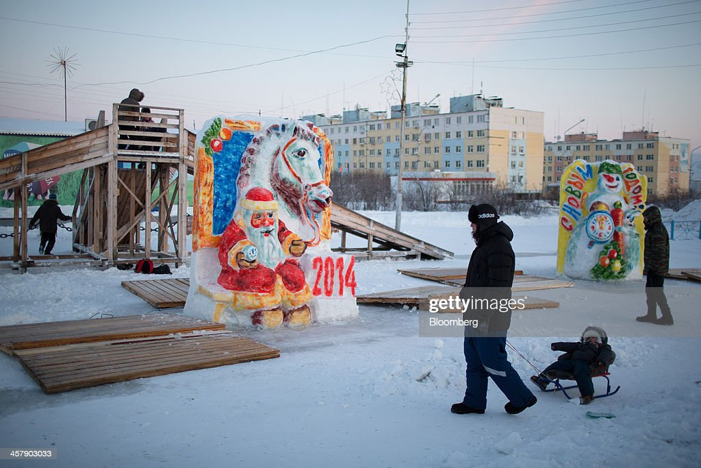 Children and their parents play on climbing frames beside Christmas snow in a frozen playground near their apartments in Udachny, Sakha Republic, Russia, on Saturday, Dec. 14, 2013. Russia plans to maintain control of Mirny-based Alrosa, which produces a quarter of the world's diamonds by value and more rough diamonds than De Beers by carat. Photographer: Andrey Rudakov/Bloomberg via Getty Images