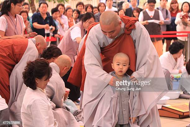 Children are dressed in robes by monks during the 'Children Becoming Buddhist Monks' ceremony forthcoming buddha's birthday at a Chogye temple on May...
