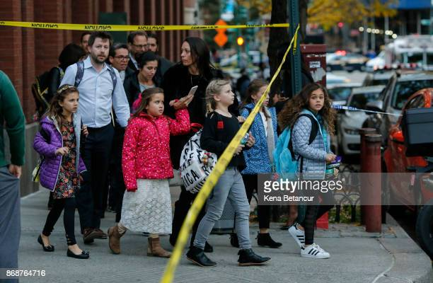 Children are evacuated from a school as emergency personal respond after a man driving a rental truck struck and killed eight people on a jogging and...