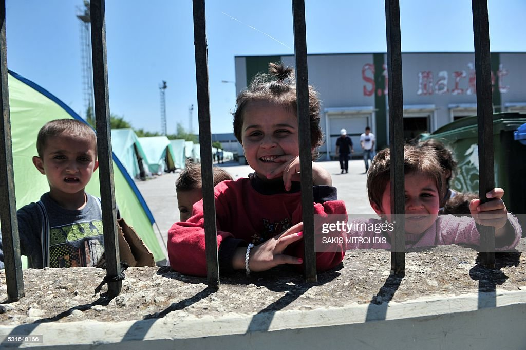 Children are pictured inside a new camp for refugees and migrants set in an abandoned factory in Sindos, a west suburb of Thessaloniki on 27 May, 2016. The squalid Idomeni refugee camp in northern Greece which became a symbol of Europe's migrant crisis has been fully evacuated, police said Thursday, as another 30 died crossing the Mediterranean. In the space of three days, police transferred about 4,000 migrants by bus from Idomeni to newly created camps in the industrial outskirts of Greece's second city Thessaloniki. / AFP / SAKIS