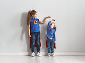 Two little children are playing superhero. Kids are measuring the growth on the background of wall. Girl power concept.