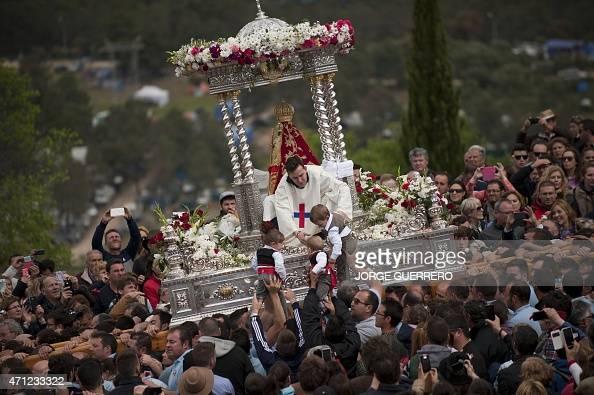 Children are presented to an effigy of the virgin Morenita displayed on a float during the 'Romeria de la Virgen de la Cabeza' annual Romeria...