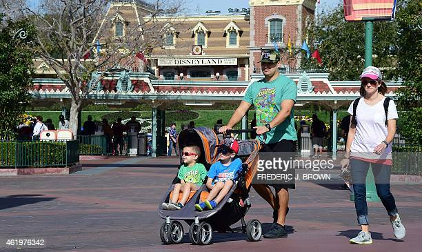 Children are pushed in their stroller as a family visits Disneyland on January 22 2015 in Anaheim California The theme park known as 'The Happiest...