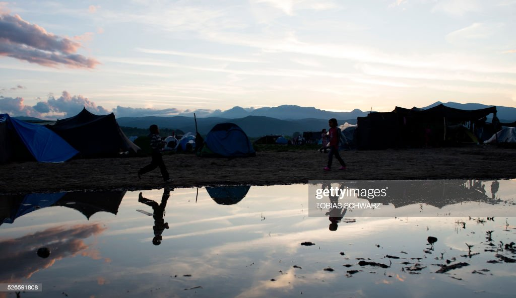 Children are reflected in a puddle at a makeshift camp for migrants and refugees near the village of Idomeni not far from the Greek-Macedonian border on April 30, 2016. Some 54,000 people, many of them fleeing the war in Syria, have been stranded on Greek territory since the closure of the migrant route through the Balkans in February. / AFP / TOBIAS