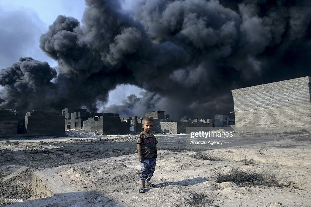 Children are seen at the street as smoke rise from oil wells, were set on fire by Daesh terrorists to limit coalition forces pilots' eyesight and to make the wells out o service following Iraqi army's retaking of Al Qayyarah town from Daesh during the operation to retake Iraq's Mosul from Daesh, in Mosul, Iraq on October 25, 2016. Black smoke affects human life in town badly.
